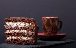 Piece of chocolate cake and cup of coffee on slate plate on blac Stock Photography