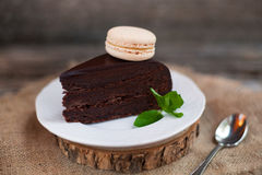 A piece of chocolate cake with fresh mint on the table, close-up Stock Images