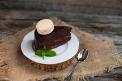 A piece of chocolate cake with fresh mint on the table, close-up Royalty Free Stock Photo