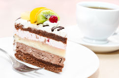 Piece of chocolate cake with fruit on plate Stock Photos