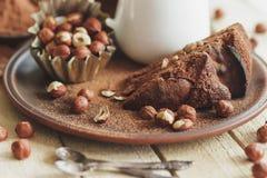 Piece of chocolate cake, hazelnuts and jar with milk