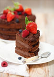 Piece of chocolate cake with icing and fresh berry. On light background Stock Photography