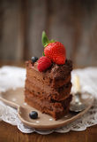 Piece of chocolate cake with icing and fresh berry. On wooden background Royalty Free Stock Image