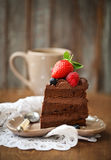 Piece of chocolate cake with icing and fresh berry. On wooden background Royalty Free Stock Photography