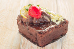 Piece of chocolate cake with icing and fresh berry on wooden bac. Kground Stock Photos