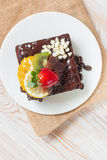Piece of chocolate cake with icing and fresh berry on wooden bac Stock Image