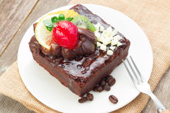 Piece of chocolate cake with icing and fresh berry. On wooden background Stock Photography