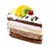 Piece of chocolate cake with icing and fresh fruit isolated. On a white background Royalty Free Stock Photography