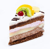 Piece of chocolate cake with icing and fresh fruit isolated on a. White background Stock Photography