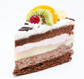 Piece of chocolate cake with icing and fresh fruit. Isolated on a white background Stock Images