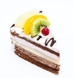 Piece of chocolate cake with icing and fresh fruit isolated on a. White background Stock Photos