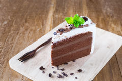 Piece of chocolate cake with icing on wooden Stock Photo