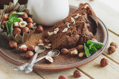 Piece of chocolate cake, mint leaves, hazelnuts and jar with milk Royalty Free Stock Photo