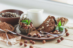 Piece of chocolate cake, mint leaves, hazelnuts and jar with milk Royalty Free Stock Photography