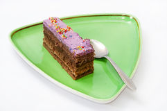 A piece of chocolate cake with peel on a green plate Royalty Free Stock Images