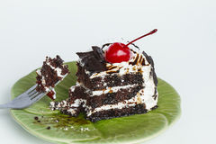 Piece of chocolate cake with red cherry Royalty Free Stock Image