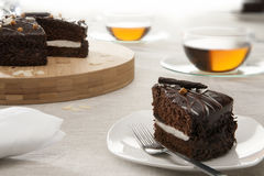 Piece of chocolate cake on saucer with tea Stock Photos