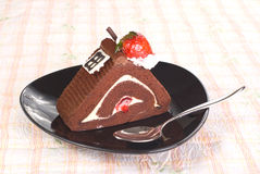 Piece of Chocolate cake with strawberry. In black  plate on the table Stock Photography