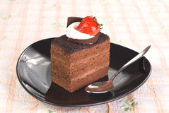 Piece of Chocolate cake with strawberry. In black  plate on the table Royalty Free Stock Photo