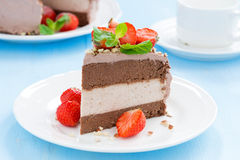 Piece of chocolate cake of three layers with fresh strawberries. Close-up Stock Photo