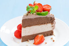 Piece of chocolate cake of three layers with fresh strawberries. On a plate, horizontal Stock Photos
