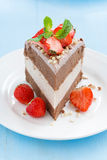 Piece of chocolate cake of three layers with fresh strawberries. On white plate, selective focus, vertical Royalty Free Stock Photos