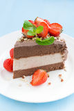 Piece of chocolate cake of three layers with fresh strawberries. On white plate, vertical Stock Images