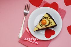 Piece of Chocolate Cake for Valentine`s day. Red Paper Hearts Arround Cake. Pink Background. Pink Napkin and Candles. Piece of Chocolate Cake for Valentine`s stock image