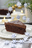 Piece of chocolate cake in white christmas table setting Stock Photos