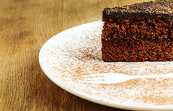 Piece of chocolate cake in a white plate with cocoa powder Stock Image