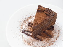 Piece of chocolate cake  on white plate. Slice of fresh brownie arranged on white plate. Copy space for your text. Selective focus on the front Royalty Free Stock Photography