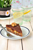 A piece of chocolate and caramel tart with walnuts Royalty Free Stock Photos
