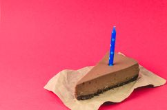 A piece of Chocolate cheesecake with blue candle on a red background stock images