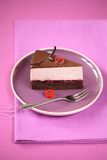 Piece of Chocolate Cherry Mousse Cake, on a purple plate. With a silver fork, on a purple tablecloth Stock Photos