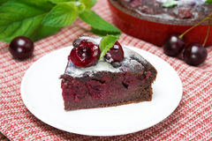 Piece of chocolate Clafoutis with cherries and powdered sugar Royalty Free Stock Photos