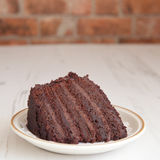 A piece of chocolate fudge cake on a wooden table Stock Photos