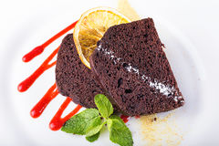 Piece of chocolate pie. Piece of chocolate cake on a plate, decorated with berry topping, mint and slice of lemon Royalty Free Stock Photos