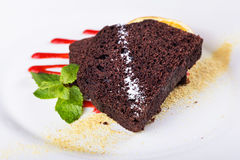 Piece of chocolate pie. Piece of chocolate cake on a plate, decorated with berry topping, mint and slice of lemon Stock Images