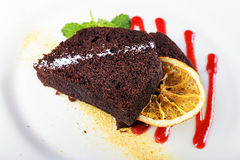 Piece of chocolate pie. Piece of chocolate cake on a plate, decorated with berry topping, mint and slice of lemon Royalty Free Stock Photo