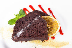 Piece of chocolate pie. Piece of chocolate cake on a plate, decorated with berry topping, mint and slice of lemon Stock Image