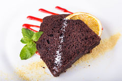 Piece of chocolate pie. Piece of chocolate cake on a plate, decorated with berry topping, mint and slice of lemon Royalty Free Stock Images