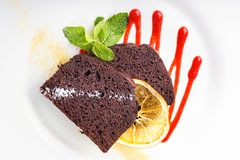 Piece of chocolate pie. Piece of chocolate cake on a plate, decorated with berry topping, mint and slice of lemon Stock Photography