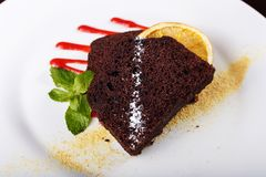 Piece of chocolate pie. Piece of chocolate cake on a plate, decorated with berry topping, mint and slice of lemon Stock Photos