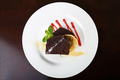 Piece of chocolate pie. Piece of chocolate cake on a plate, decorated with berry topping, mint and slice of lemon Royalty Free Stock Photography
