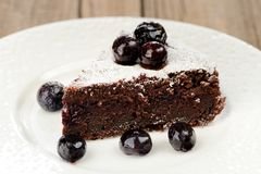 Piece of chocolate pie with whole blueberries and icing sugar in Royalty Free Stock Images