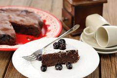 Piece of chocolate pie with whole blueberries and icing sugar in Stock Images