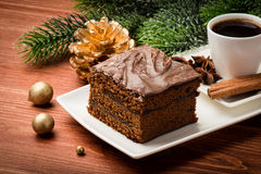 A piece of  christmas gingerbread cake on the white plate on the festive table. A piece of  christmas gingerbread cake on the plate on the festive table Royalty Free Stock Image