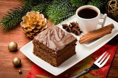 A piece of  christmas gingerbread cake on the white plate on the festive table. A piece of  christmas gingerbread cake and a cup of coffee on the white plate on Royalty Free Stock Images