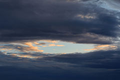 Piece of clear blue sky surrounded by storm clouds Stock Images