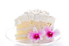 A piece of coconut cake with two orchids Stock Image